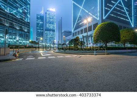 clean road against illuminated buildings in shanghai. - stock photo