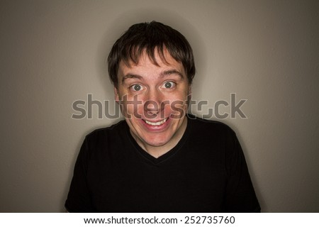 clean shaven young man doing a weird creepy smile