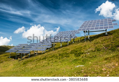 clean solar power panels on a nature green meadow in mountain scenery with blue sky and white clouds - stock photo