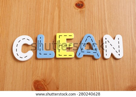 CLEAN, spell by woody puzzle letters with woody background