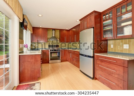 Clean style kitchen with stained wood cabinets, and nice counter tops.