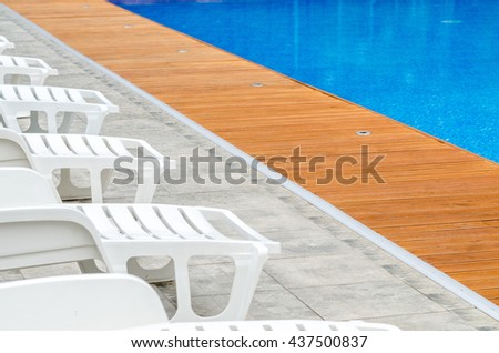 clean swimming pool and empty resting chair