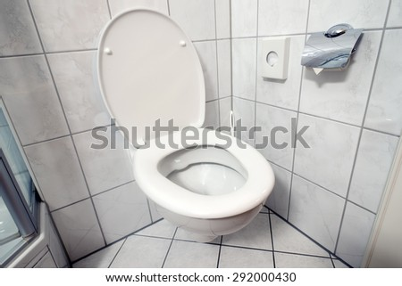 clean toilet room corner with open seat cover