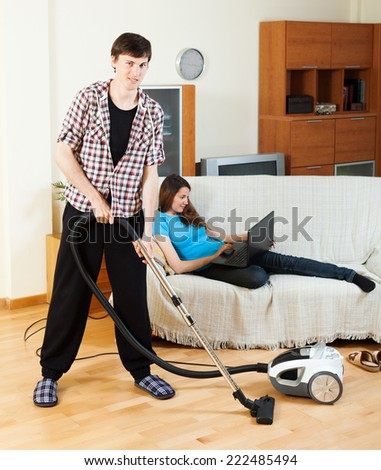 Clean up man, while wife lying with notebook on the sofa at home