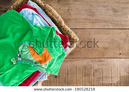 Clean washed unironed summer clothes with a fresh fragrance stacked in a wicker laundry basket with a bright green shirt on top, overhead view on rustic wooden boards with copys pace to the right - stock photo