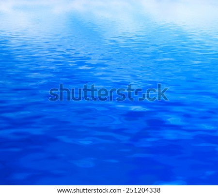 Clean water background with calm waves. Blue sky reflection - stock photo