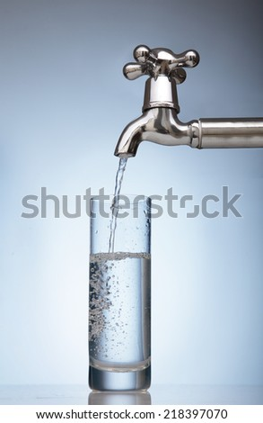 clean water is poured into a glass from the tap - stock photo