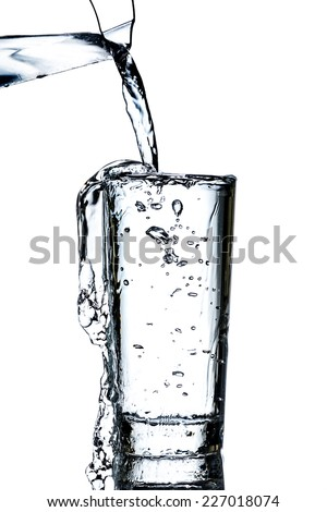 Clean water poured from a jug into a glass over white background - stock photo