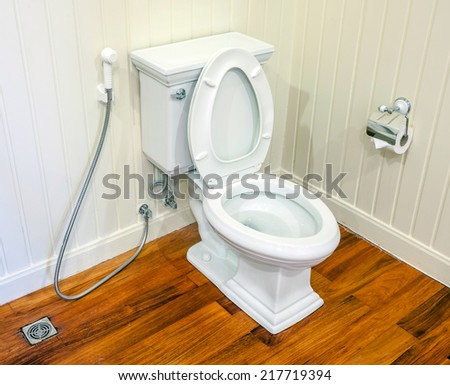 Clean, white and sterile toilet in a white wall bathroom and wood floor. - stock photo