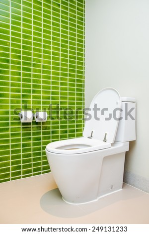 Clean, white  toilet and paper rolls with Lime green mosaic tiles wall in bathroom