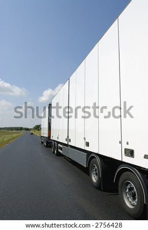 clean white truck on straight country-road, seen from ground-level and behind - stock photo