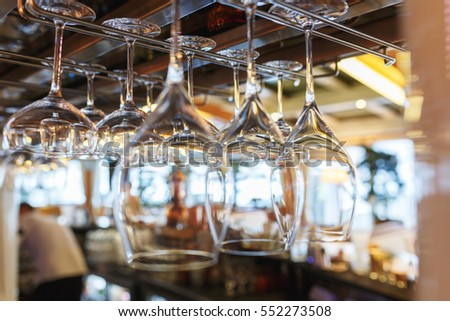 Clean wine glasses prepared by bartender and hung on the bar at a restaurant or cafe. Glasses prepared for a party at the bar.