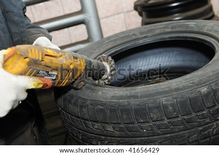 cleaning a car wheel tyre by mechanical metal brush - stock photo