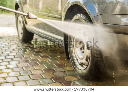 Cleaning a car with a high pressure washer - stock photo