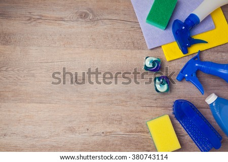 Cleaning and housework concept with supplies on wooden background. View from above with copy space - stock photo