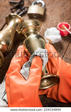 cleaning and polishing old brass jar - stock photo