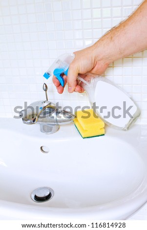 Cleaning bathroom sink with spray bottle - stock photo