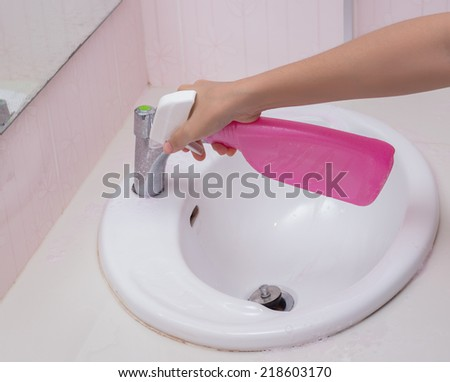 Cleaning bathroom sink with spray bottle.