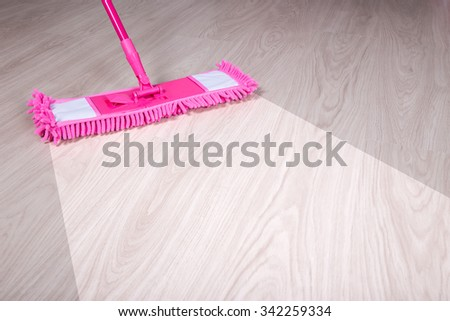 cleaning, before and after concept - close up of wooden floor with pink mop - stock photo