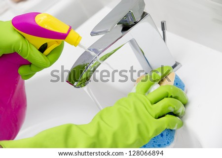 Cleaning - cleaning bathroom sink with spray detergent - housework, spring cleaning concept - stock photo