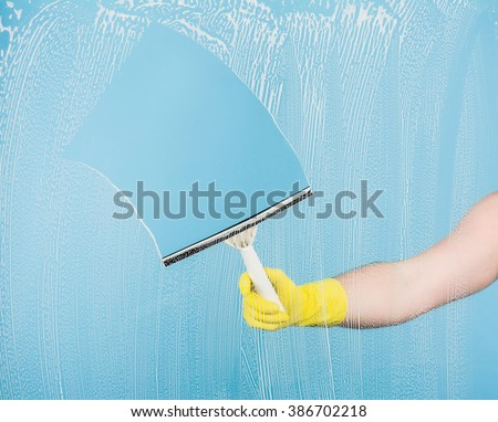 Cleaning concept - hand cleaning glass window pane with detergent and rubber aluminum wiper - stock photo