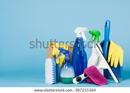 Cleaning concept - mixed detergents and cleaning accessories isolated on blue seamless background. - stock photo