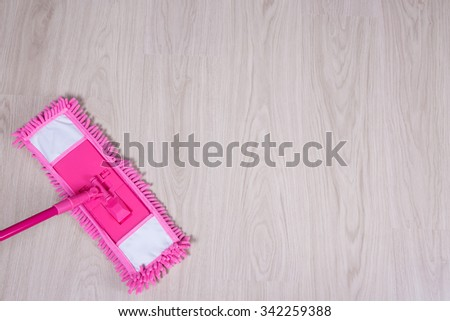 cleaning concept - pink mop on wooden parquet floor - stock photo