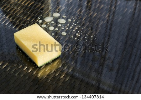 Cleaning glass sufrace table: yellow sponge over scour liquid composition - stock photo