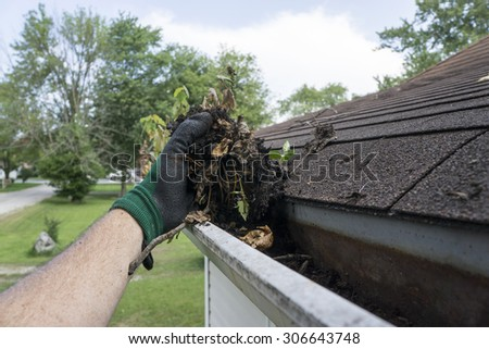 Cleaning gutters filled with leaves and sticks. - stock photo