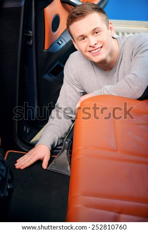 Cleaning in the car. Closeup shot of handsome smiling young man vacuuming his car with a car vacuum cleaner  - stock photo