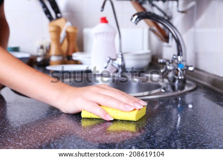 Cleaning kitchen with sponge - stock photo