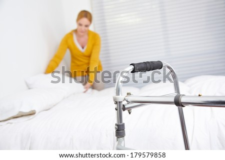 Cleaning lady doing housekeeping in nursing home with walker in front - stock photo
