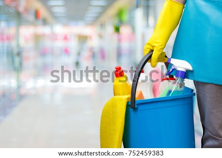Cleaning lady with a bucket and cleaning products on blurred background.
