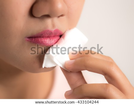 Cleaning lotion make-up remover with cotton pads. Lips close-up