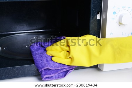 Cleaning microwave oven in kitchen close-up - stock photo