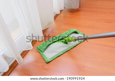 cleaning mop in cleaning action on bedroom wooden floor - stock photo