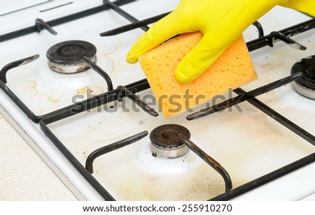 cleaning of dirty gas stove burners in kitchen room - stock photo