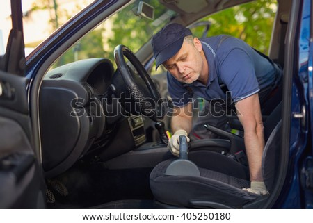 Cleaning of interior of the car with vacuum cleaner - stock photo