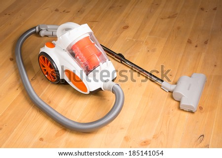 Cleaning of the apartment. Vacuum cleaner on the wooden floor - stock photo
