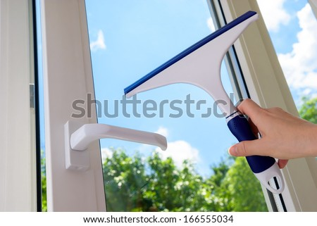 cleaning open plastic vinyl window on a background blue sky - stock photo