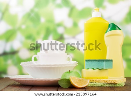 Cleaning products and clean dishes on green background - stock photo