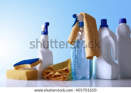 Cleaning products and equipment on white table and blue background overview. Front view. Horizontal composition. - stock photo
