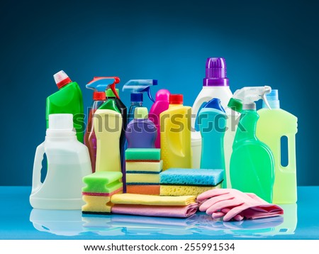 cleaning products and supplies on table with blue background - stock photo