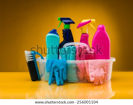 cleaning products and utensils in plastic basin against yellow background - stock photo