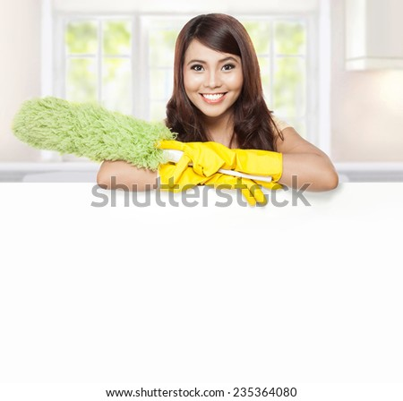 Cleaning service woman presenting a blank board and hold a duster - stock photo