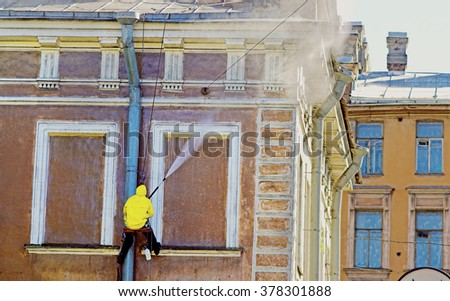 Cleaning service worker washing old building facade - stock photo