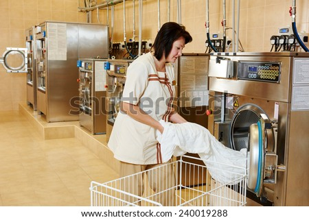 cleaning services. Woman loading laundry washing machine with cloth - stock photo