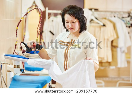 cleaning services. Woman with iron working at ironing shop - stock photo
