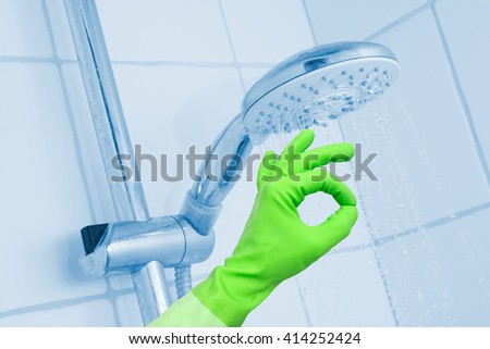 Cleaning shower with glove on - stock photo