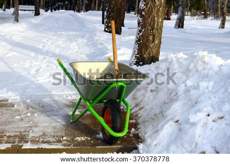 Cleaning sidewalks of snow, Sprinkling sand. Pushcart with shovel - stock photo